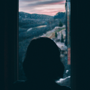 woman with depression staring out the window seeking help